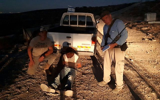 Jewish farmers pose next to a Palestinian man who tried to attack the owner of Talia Farm in the West Bank on October 24, 2017. (Har Hebron Regional Council)