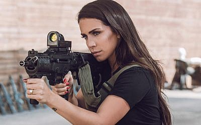 Orin Julie posing with an assault rifle at a shooting range in the West Bank. (Omer Shapira/Courtesy of Say Talent)