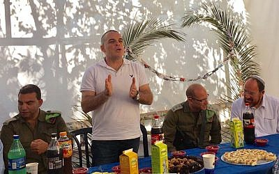 Efrat Mayor and settlements advocate Oded Revivi speaks to a gathering of Israelis and Palestinians at his sukkah in Efrat, October 11, 2017. (Courtesy Yesha Council)