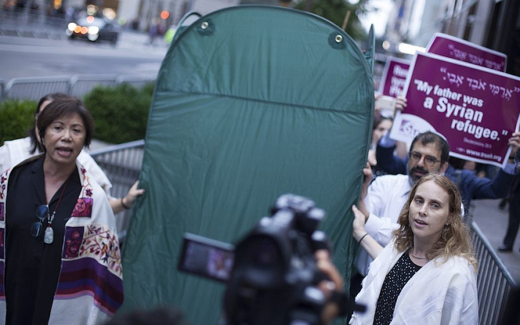 Rabbis from T'ruah: The Rabbinic Call for Human Rights, carry a pop-up sukkah in a demonstration for immigrants' rights outside the Trump Tower in New York, October 9, 2017. (Courtesy of T'ruah)