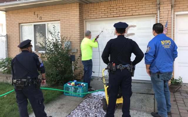 New York police crew members removing a swastika from a garage in Staten Island. (NYPD 23rd Precinct via JTA)