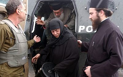 An Israeli soldier helps to smuggle out a priest and nun from the Church of the Nativity in Bethlehem on Sunday April 7, 2002. Israeli soldiers have been outside the church for a week long standoff with Palestinian gunmen. Photo by Flash90.