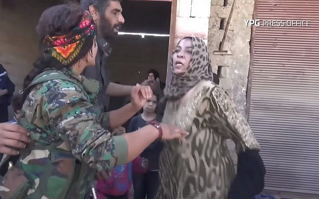 Woman rips off Islamic State-imposed black cloak in celebration, at liberation of Raqqa, October 13, 2017. (Screen capture: YouTube, YPG)