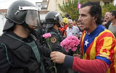 A man offers a carnation to a Spanish Guardia Civil guard in Sant Julia de Ramis, on October 1, 2017, on the day of a referendum on independence for Catalonia banned by Madrid. (AFP PHOTO / LLUIS GENE)