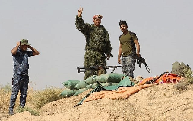 Iraqi forces gesture from a river bank across from Kurdish peshmerga positions on October 14, 2017, on the southern outskirts of Kirkuk. (AFP PHOTO / AHMAD AL-RUBAYE)