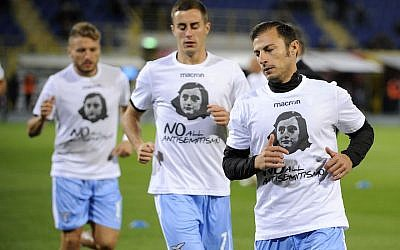 "Lazio players wear a shirt depicting Anne Frank saying ""No to anti-Semitism,"" in response to anti-Semitic stickers left by their fans at a previous match, during the Serie A match between Bologna FC and SS Lazio at Stadio Renato Dall'Ara in Bologna, Italy, on October 25, 2017. (Marco Rosi/Getty Images via JTA)"