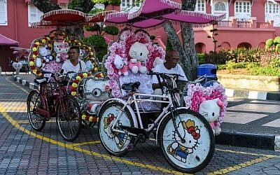 Riders wait for customers on trishaws with Hello Kitty decorations in Malaysia's historical city of Malacca on October 6, 2017. (AFP PHOTO / Mohd RASFAN)