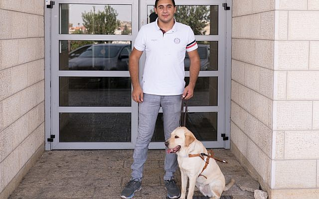 Saleem Sharif, with Winston, outside the health clinic in Nazareth where he works. (Luke Tress/Times of Israel)