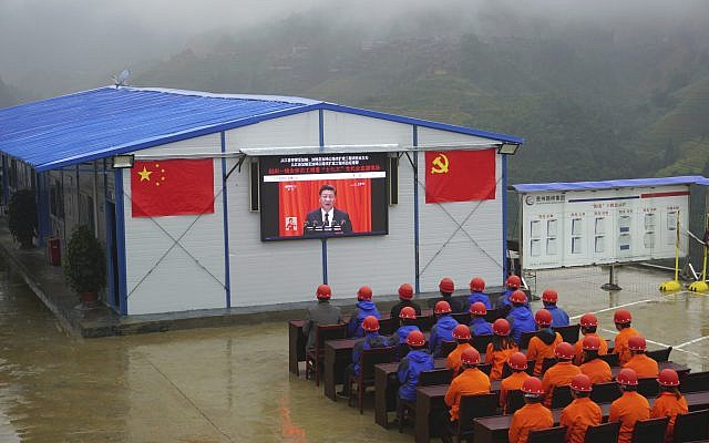Road construction workers watch a screen showing a speech by Chinese President Xi Jinping during the opening ceremony of the 19th Party Congress in Congjiang county in southwestern China's Guizhou province Wednesday, Oct. 18, 2017. (Chinatopix via AP)