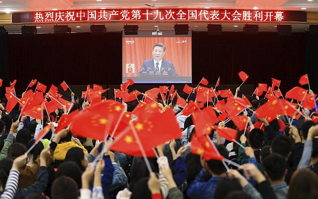Students wave flags as they watch a speech by Chinese President Xi Jinping during the opening ceremony of China's 19th Party Congress in Huaibei in eastern China's Anhui province October 18, 2017. (Chinatopix via AP)