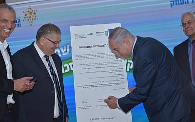 Prime Minister Benajmin Netanyahu (r) signs a deal for new housing in the northern town of Migdal Haemek on November 6, 2017. (Migdal Haemek)