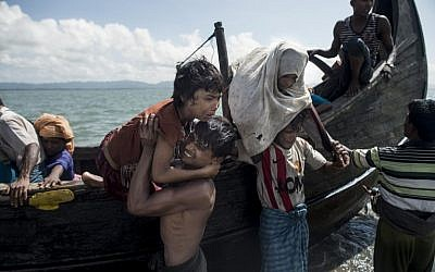Bangladeshi men help Rohingya Muslim refugees to disembark from a boat on the Bangladeshi shoreline of the Naf river after crossing the border from Myanmar in Teknaf on September 30, 2017. (AFP PHOTO / FRED DUFOUR)