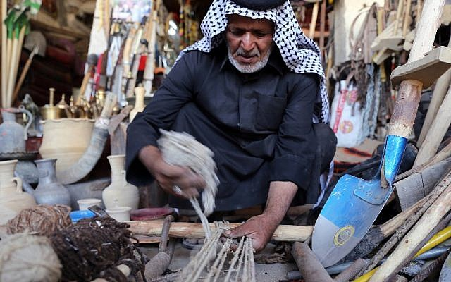 An Iraqi man weaves a carpet at his textile workshop in the Iraqi city of Hilla, south of Baghdad, on October 12, 2017. (AFP Photo/Sabah Arar)
