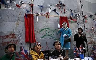 An actor dressed up as Queen Elizabeth and Palestinian children from the al-Ayda refugee camp attend an event organized by secretive British street artist Banksy to apologize for the 100th anniversary of the Balfour Declaration on November 1, 2017 at his Walled-Off Hotel in Bethlehem in the West Bank. (AFP/Ahmad Gharabli)