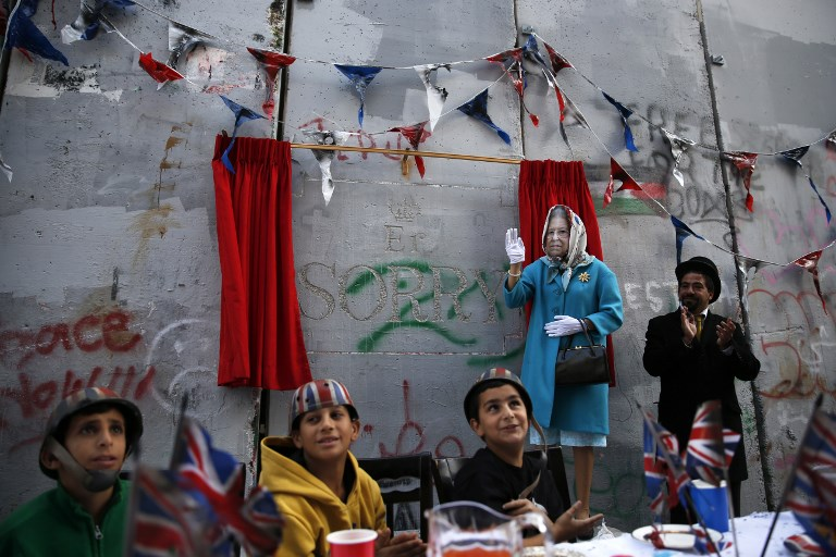 Banksy holds balfour apology party for palestinians the times an actor dressed up as queen elizabeth and palestinian children from the al ayda refugee ccuart Choice Image