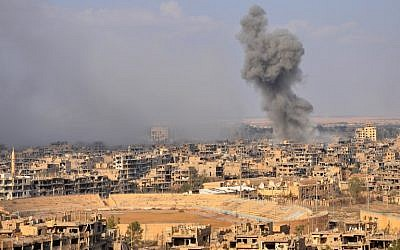 Illustrative: Smoke billows from the eastern city of Deir Ezzor during an operation by Syrian government forces against Islamic State (IS) group jihadists on November 2, 2017. (AFP/Stringer)
