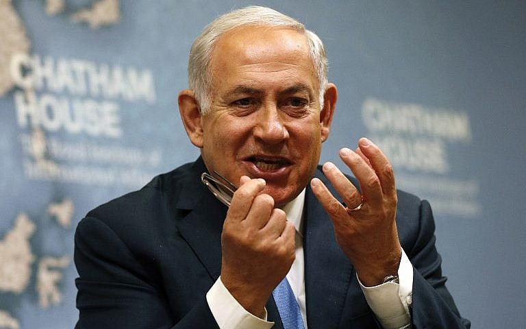 Prime Minister Benjamin Netanyahu gestures while giving a lecture regarding Israel's foreign policy priorities at Chatham House The Royal Institute of International Affairs in Lond