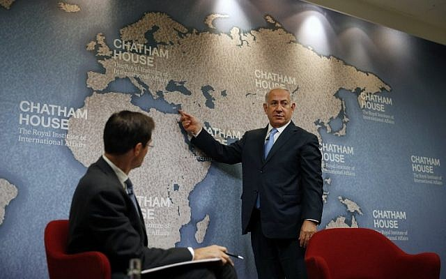 Israeli Prime Minister Benjamin Netanyahu gestures towards countries on a map while giving a lecture regarding Israel's foreign policy priorities as Chatham House Director Robin Niblett looks on at Chatham House, The Royal Institute of International Affairs, in London November 3, 2017. (AFP PHOTO / ADRIAN DENNIS)