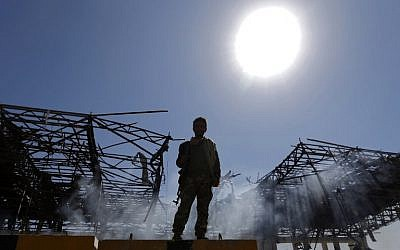 Illustrative: A Houthi fighter inspects the site of an air strike in the Yemeni capital Sana'a, on November 5, 2017. (AFP Photo/Mohammed Huwais)