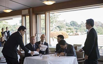 "Staff members help as US President Donald Trump,left, signs hats that say ""Make Alliance Even Greater"" with Japanese Prime Minister Shinzo Abe, right, during a luncheon at the Kasumigaseki Country Club Golf Course in Kawagoe, Saitama prefecture, outside Tokyo on November 5, 2017. (AFP/JIM WATSON)"