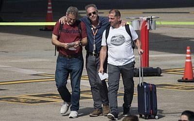 Argentine survivors of the recent New York bike path truck attack, Juan Pablo Trevisan (L) and Ariel Benvenuto (R), are greeted by an unidentified man upon their arrival in Rosario on November 6, 2017. (AFP Photo/STR)