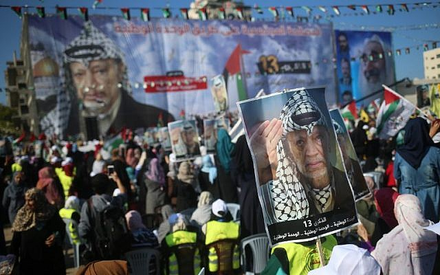 Palestinians hold pictures of Yasser Arafat in Gaza City on November 9, 2017. (AFP Photo/Mohammed Abed)
