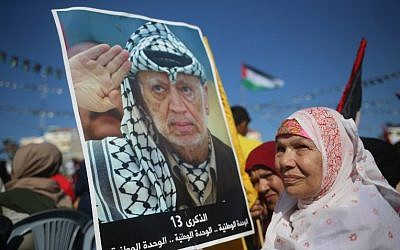 Palestinians hold pictures of late leader Yasser Arafat in Gaza City on November 9, 2017, during a festival to commemorate the 13th anniversary of his death. (AFP PHOTO / MOHAMMED ABED)