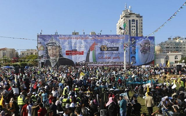 Palestinians hold pictures of late leader Yasser Arafat in Gaza City on November 9, 2017, during a festival to commemorate the 13th anniversary of his death. A billboard with a picture of late Hamas leader Sheikh Ahmed Yassin is seen on the right. (AFP PHOTO / MOHAMMED ABED)