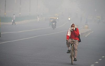 An Indian man rides a bike amid heavy smog on a street of New Delhi on November 10, 2017. (AFP/DOMINIQUE FAGET)