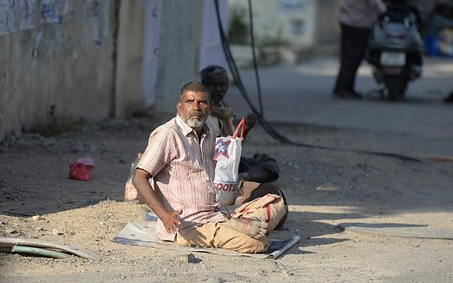 An Indian man begs on the side of the road in Hyderabad on November 10, 2017. (AFP PHOTO / NOAH SEELAM)