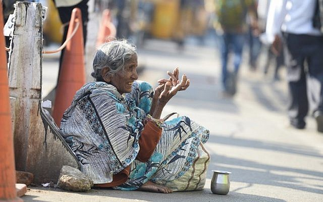 An Indian woman begs on the side of the road in Hyderabad on November 10, 2017. (AFP PHOTO / NOAH SEELAM)