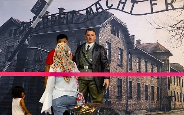 This photograph taken on November 10, 2017 shows an Indonesian family preparing to take a photograph with a life-size wax sculpture of Adolf Hitler at a museum in Yogyakarta (AFP / HENRYANTO)