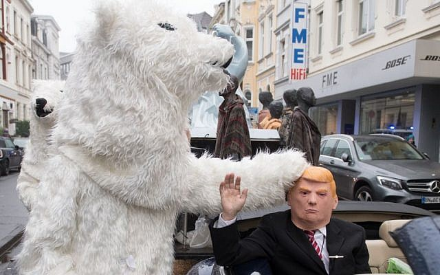 "A demonstrator dressed as US President Donald Trump waves from a car as he parades with other activists dressed as polar bears during a protest of the action group ""No Climate Change"" on November 11, 2017, in Bonn, Germany, where is taking place the COP23 United Nations Climate Change Conference. (AFP PHOTO / dpa / Bernd Thissen)"
