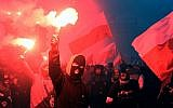 Demonstrators burn flares and wave Polish flags during the annual march to commemorate Poland's National Independence Day in Warsaw on November 11, 2017. (AFP PHOTO / JANEK )