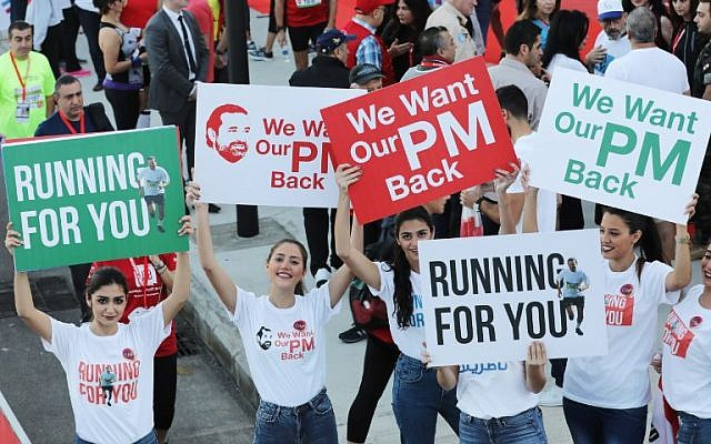 Supporters of Lebanon's Prime Minister Saad Hariri hold up posters demanding his return from Saudi Arabia, on the starting line of Beirut's annual marathon, on November 12, 2017. (AFP Photo/Anwar Amro)