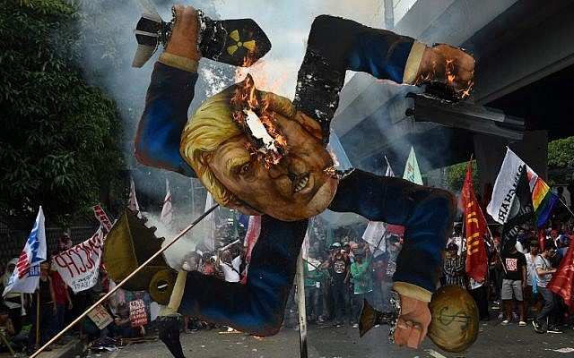 Protesters burn an effigy of Donald Trump during a protest against the US president  in Manila, on November 13, 2017. (AFP Photo/Ted Aljibe)