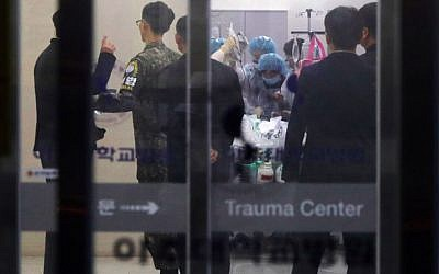 A South Korean military officer, second left, wearing an armband of the Joint Security Area of Panmunjom, looks on as medical members treat an unidentified injured person, believed to be a North Korean soldier who defected, at a hospital in Suwon, south of Seoul, on November 13, 2017. (AFP/YONHAP)
