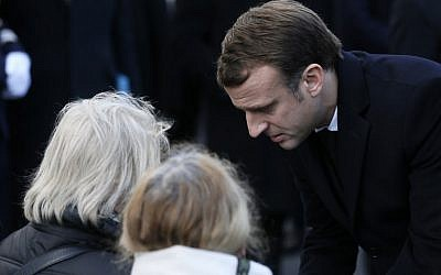 French President Emmanuel Macron speaks to relatives of victims near the 'Le Carillon' bar and 'Le Petit Cambodge' restaurant during a ceremony marking the second anniversary of the Paris attacks of November 2015 in which 130 people were killed, in Paris on November 13, 2017. (Etienne Laurent/AFP)