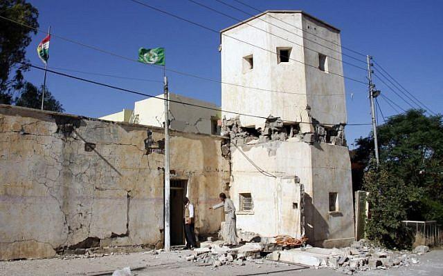 People inspect a damaged building in the mountainous town of Darbandikhan, in Iraqi Kurdistan, on November 13, 2017. (AFP Photo/Shwan Mohammed)