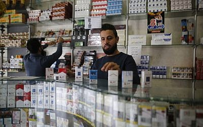 Palestinian vendors sell cigarettes at a shop in Gaza City on November 13, 2017. (AFP/MOHAMMED ABED)