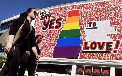 "People walk past a giant billboard promoting the ""yes"" vote for same-sex marriage in Sydney's Kings Cross district on November 14, 2017. (AFP PHOTO / William WEST)"