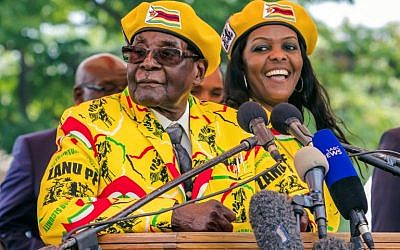 This photo taken on November 8, 2017 shows  Zimbabwe's President Robert Mugabe (L) addressing party members and supporters gathered at his party headquarters to show support to Grace Mugabe (R) becoming the party's next Vice President after the dismissal of Emerson Mnangagwa. (AFP PHOTO / Jekesai NJIKIZANA)