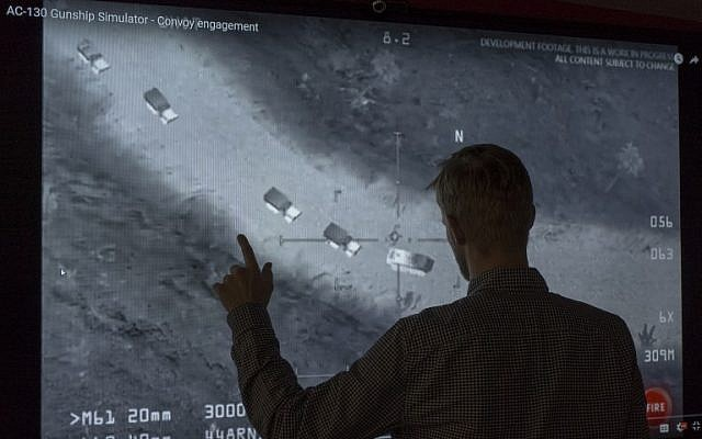 In this November 14, 2017, photo illustration a journalist in Washington, DC,  looks at YouTube video showing images from a aerial assault video game. Russia's defense ministry on Tuesday shared the same footage on its own channels saying it proved the US was aiding the Islamic State in the Middle East, but social media users pointed out they included a still from a video game. (AFP Photo/STF)
