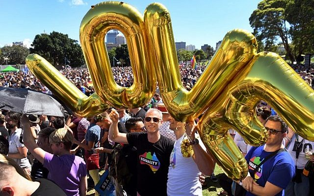 "Supporters of the same-sex marriage ""Yes"" vote gather to celebrate the announcement in a Sydney park on November 15, 2017. (AFP PHOTO / WILLIAM WEST)"