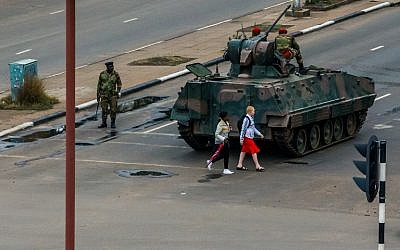 Young women walk past an armored personnel carrier that stations by an intersection as Zimbabwean soldiers regulate traffic in Harare on November 15, 2017. (AFP PHOTO)