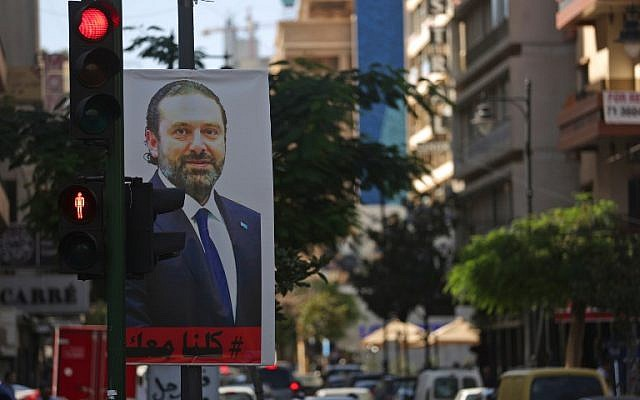 "A poster for Lebanese Prime Minister Saad Hariri is seen hanging on a traffic signal in Beirut's Hamra street on November 15, 2017. Lebanon's President Michel Aoun accused Saudi Arabia of having ""detained"" Hariri, who announced his resignation in a statement from the kingdom earlier this month. ( AFP PHOTO / Patrick BAZ)"