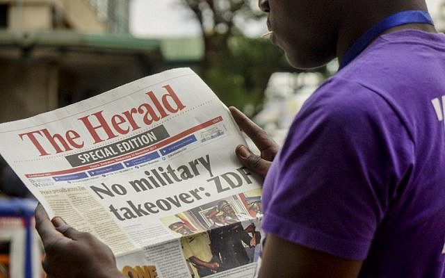 A man reads the front page of a special edition of The Herald newspaper about the crisis in Zimbabwe with the headline 'No military takeover - ZDF' on November 15, 2017 in Harare.(AFP PHOTO)