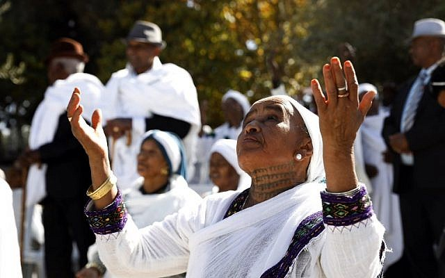 Israeli women from the Ethiopian Jewish community pray during the Sigd holiday marking the desire to 'return to Jerusalem', as they celebrate from a hilltop in the holy city overlooking the Temple Mount, on November 16, 2017. (AFP PHOTO / GALI TIBBON)