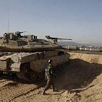 A picture taken on November 16, 2017, shows an Israeli soldier walking next to a tank at an army position overlooking southern Lebanon in the northern Israeli town of Metula, along Israel's border with Lebanon. (AFP PHOTO / MENAHEM KAHANA)