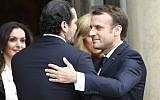 French President Emmanuel Macron (R) embraces Lebanese Prime Minister Saad Hariri (L) after their meeting at the Elysee Presidential Palace on November 18, 2017 in Paris. (AFP/Bertrand Guay)